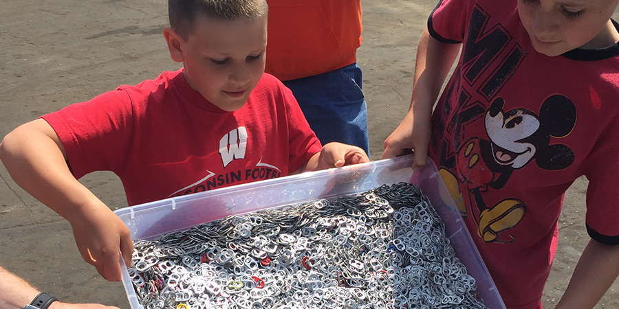 Boy Holding Container of Pop Tabs.