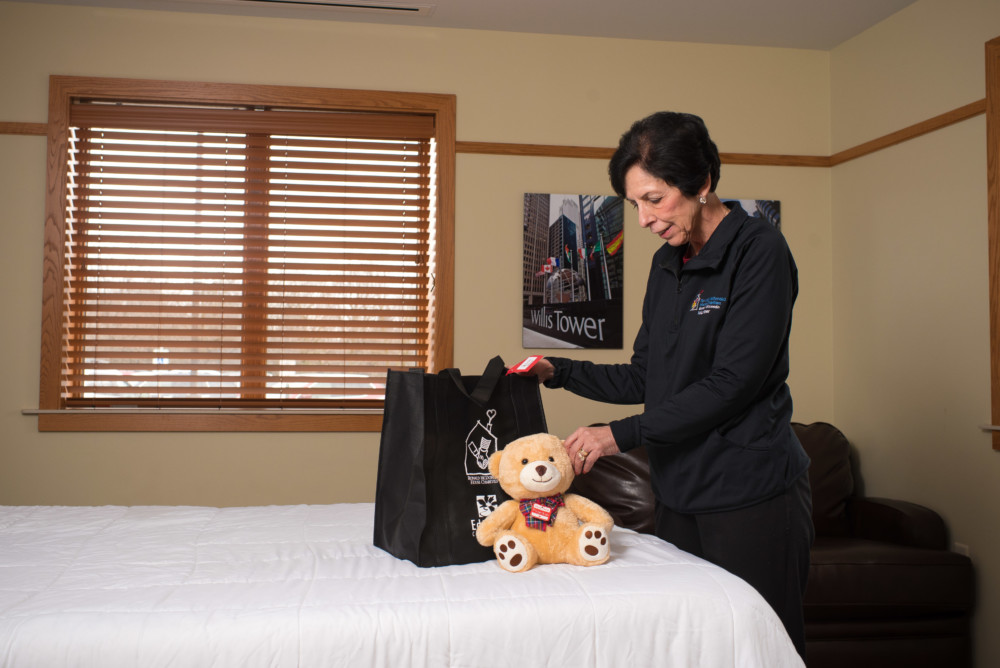 Nettie putting a hospitality bag into a guest room